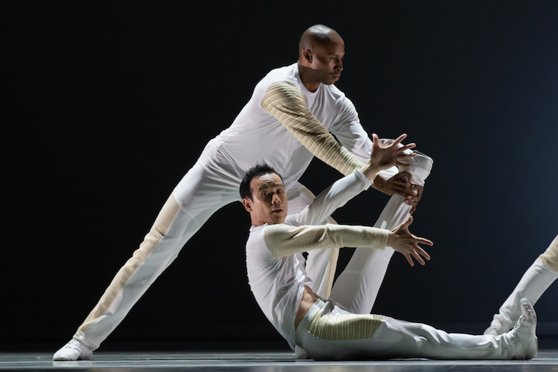 Two dancers in white. One sits on the floor with his legs straight and scissor-like. The other is in a wide stand behind him. Leaning towards his right bent leg.