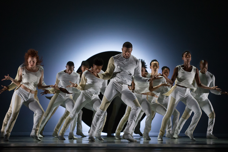 An ensemble of dancers all in white stand with their arms stretched out to their sides. Heads are down.