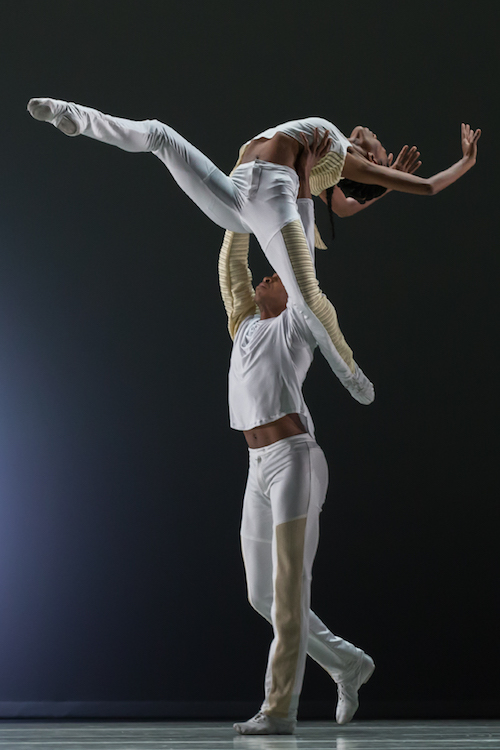 A dancer is lifted by another. Her legs stretch into attitude positions.