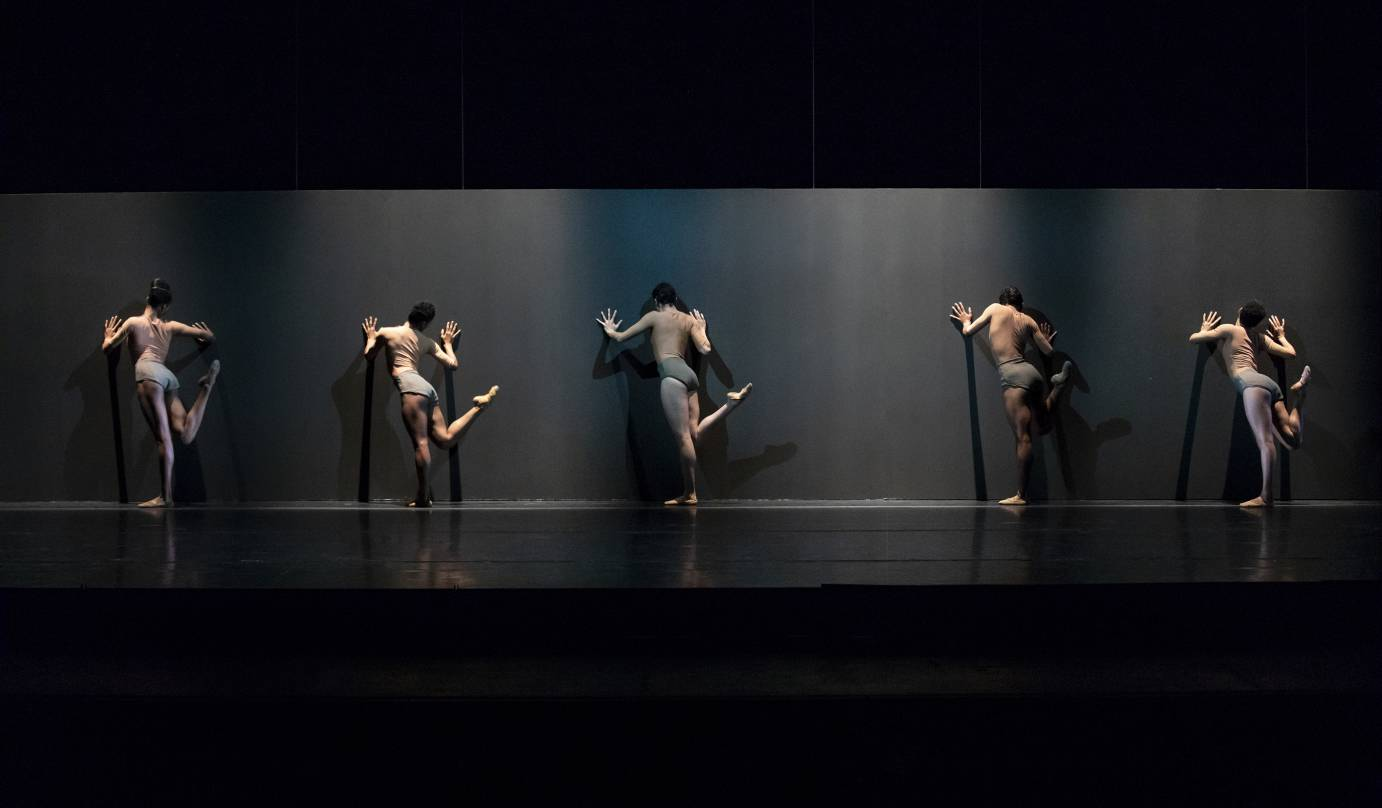 Five dancers with the their backs to the audience flick their legs