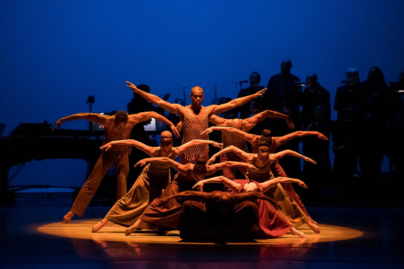 Dancers clump into a pyramid, their arms bent and extended, like wings