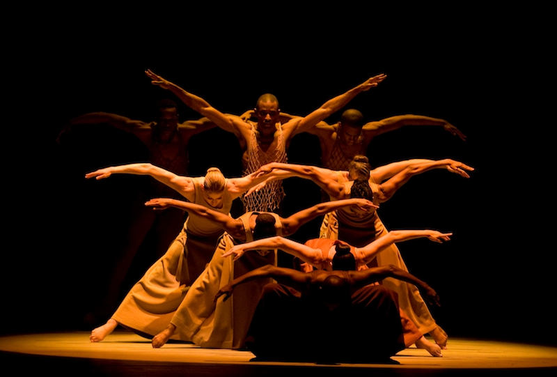A group of dancers curve their arms like birds' wings.