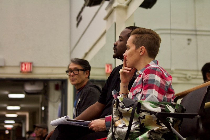 Three Ailey creatives sit against the studio mirror as they watch rehearsal. Elisa Clark sits with a notebook in hand.