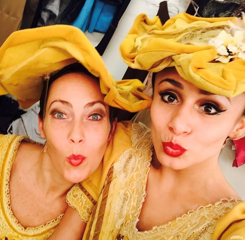 A selfie of two Ailey dancers in yellow dresses and ornate hats featured in Alvin Ailey's iconic Revelation