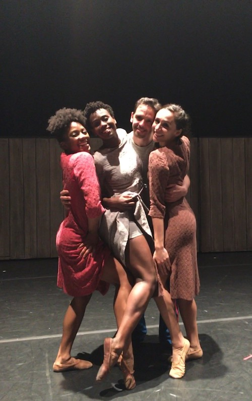Three female Ailey dancers in knit dresses pose and embrace Yvan Dubreuil