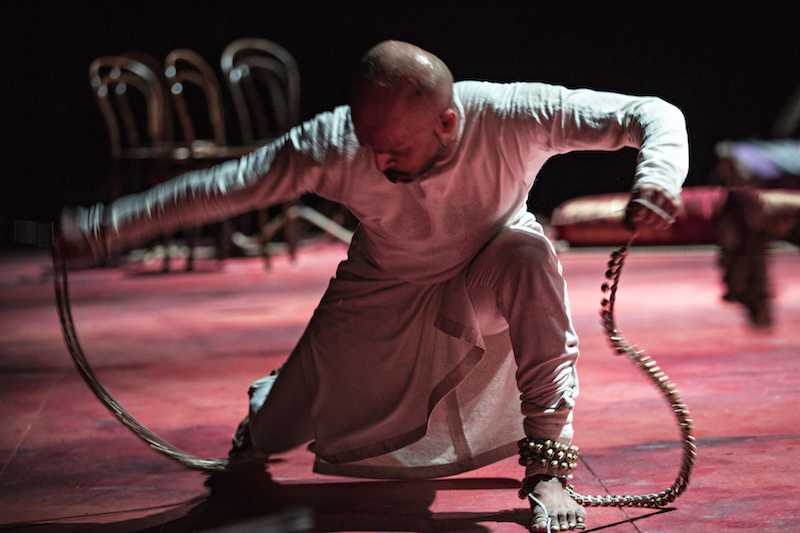 Akram Kahn crouches low to the floor. His hands hold ropes or coils that are attached to his ankles. He's wearing white.