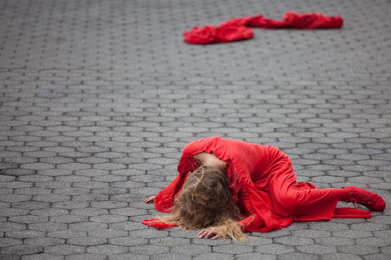 A woman in red lays on the ground. We can't see her face.