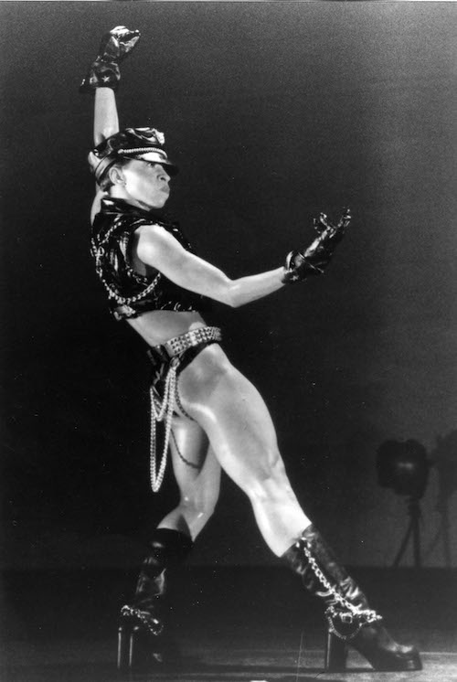 A woman in a biker-inspired costumed (leather hat, gloves, vest, briefs and boots) strikes a powerful pose. One arm is extended above her head in a fist and the other is gesturing in front of her.
