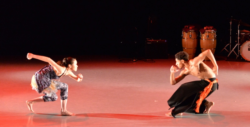 Two dancers crouch and look toward one another. The stage is brightly lit and there are percussion instruments in the background.