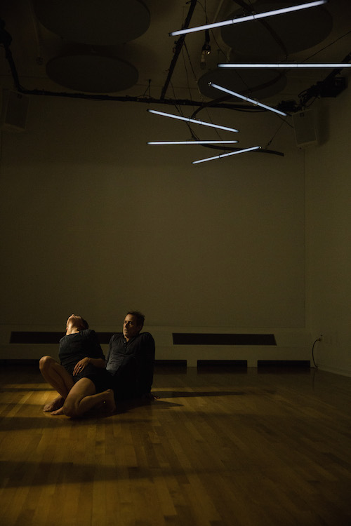 Two dancers sit in a dark room. 5 strips of lights cast a small pool light on them