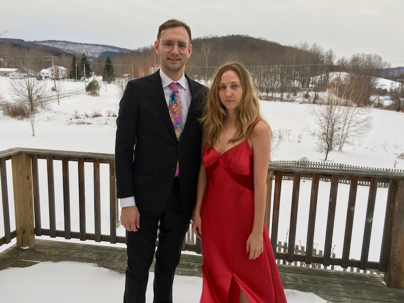 Neal Medlyn in a suit and Maggie Cloud in a red silk evening gown pose for a photo outside where there is snow and trees.