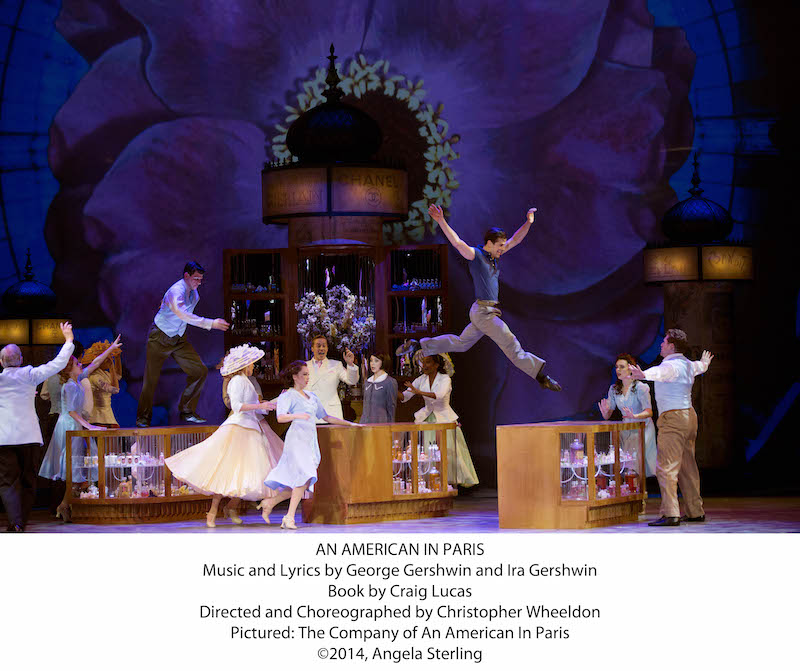 The cast of An American Paris with Robert Fairchild leapig off a table