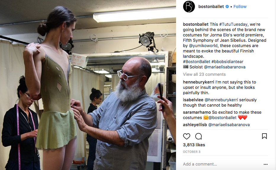 An image from Boston Ballet's instagram page. A costume designer pins a ballet dancer's olive green costume at its skirt.