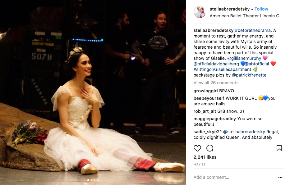 A behind-the-scenes image of American Ballet Theatre principal dancer Stella Abrera. She sits on a stone prop in a white romantic tutu. she wears knit warms up underneath.