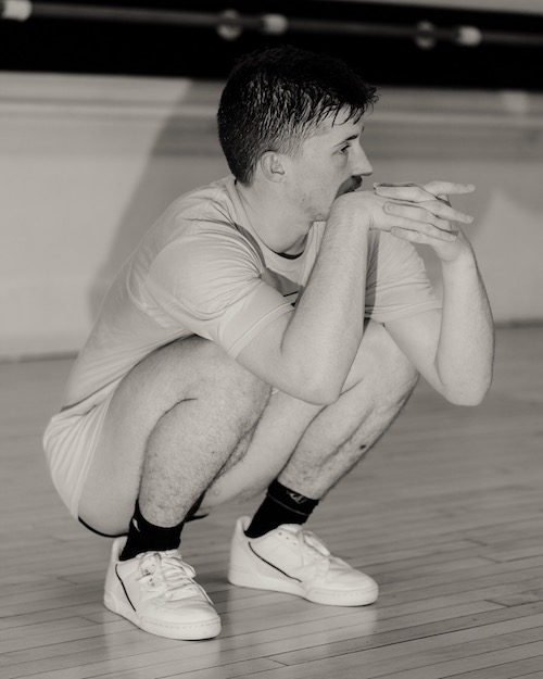 Ashley R.T. Yergens crouches near the floor. His hands are clasped near his face.