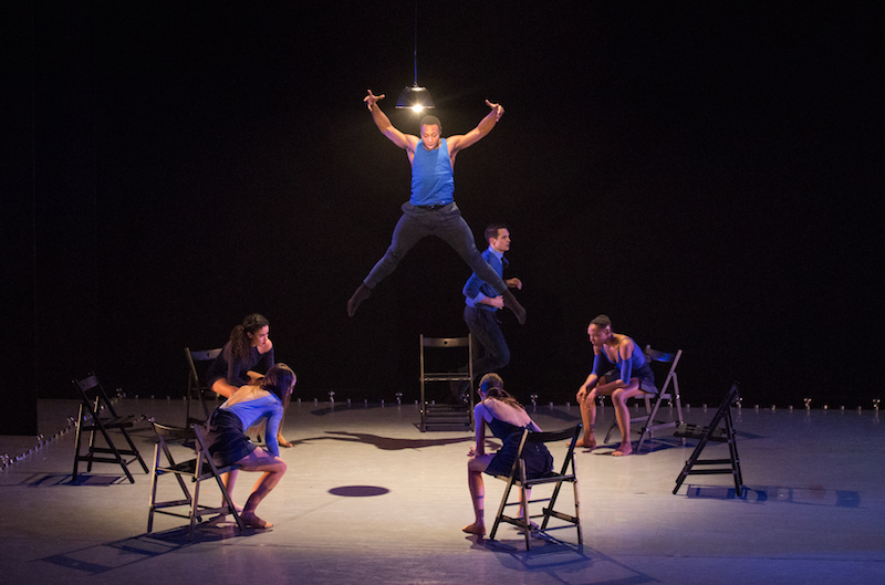 A man in a blue shirt and black slacks leaps high into the air as dancers sit in chairs in encircling the artist