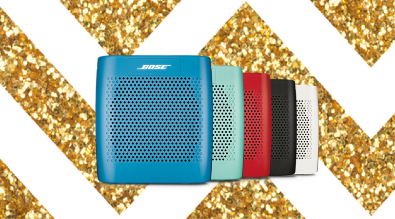 Colorful Bose Soundlink speakers are displayed in front of a gold sparkly background