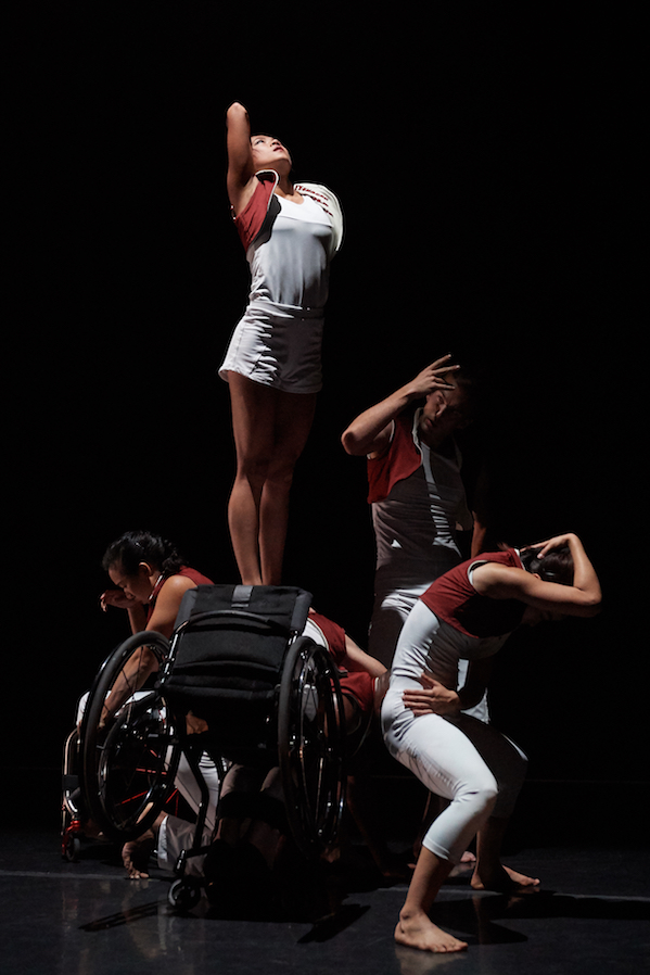 Dancers in white and red create a tall tableau. A few dancers contort around another performer in a wheelchair. One dancer stands above them.
