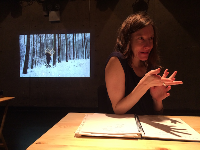 Aynsley Vandenbroucke sits in a darkened room at a desk. She looks like she is talking to someone. A video of her walking through the snowy woods with a table on her back is on in the background.