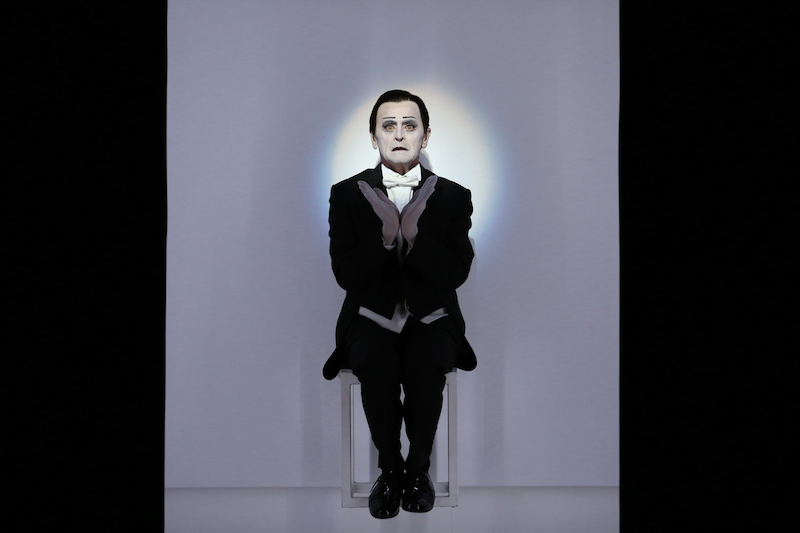 Mikhail Baryshnikov in dramatic stage makeup and tuxedo sits on a white cube. His face is illuminated by a light and the heels of his hands form a V in front of his chest.