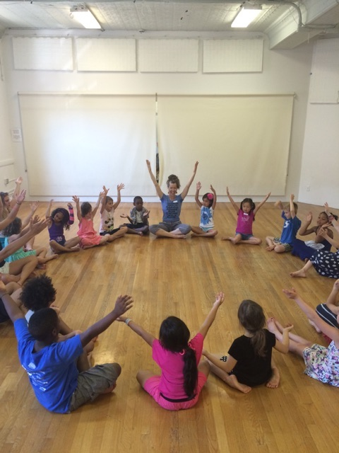 A group of kids sit in a circle with arms raised above their heads. Dance artist teacher Donna Costello leads them in the exercise.