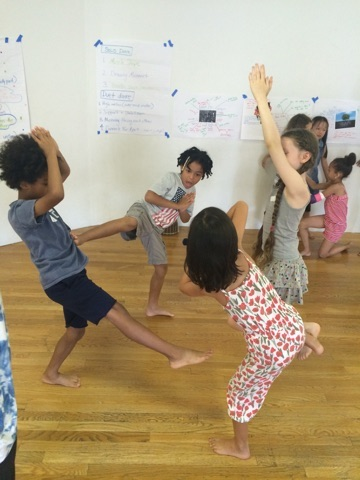 A group of kids play. One has his leg in the air. Two children have their palms together with their arms raised above their head. Another stands on one leg.