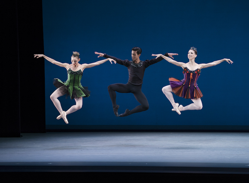 Three dancers leap in the air. Their legs make a diamond shape with their feet crossed at the ankle.