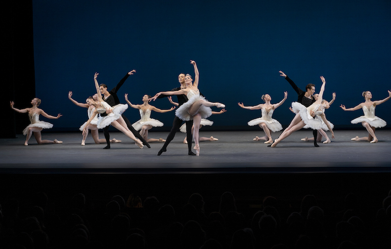 Some dancers in white tutus knee while others are partnered by male dancers in black.