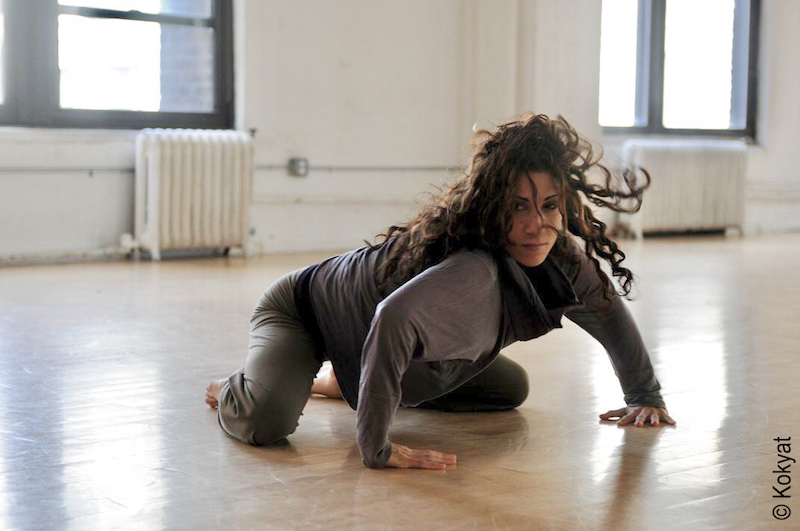 A woman crouches on the floor in grey dance clothes in a studio.