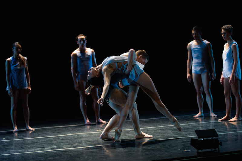 A male dancer supports a female dancer as she executes a deep back end, other dancers stand at the edges of the stage