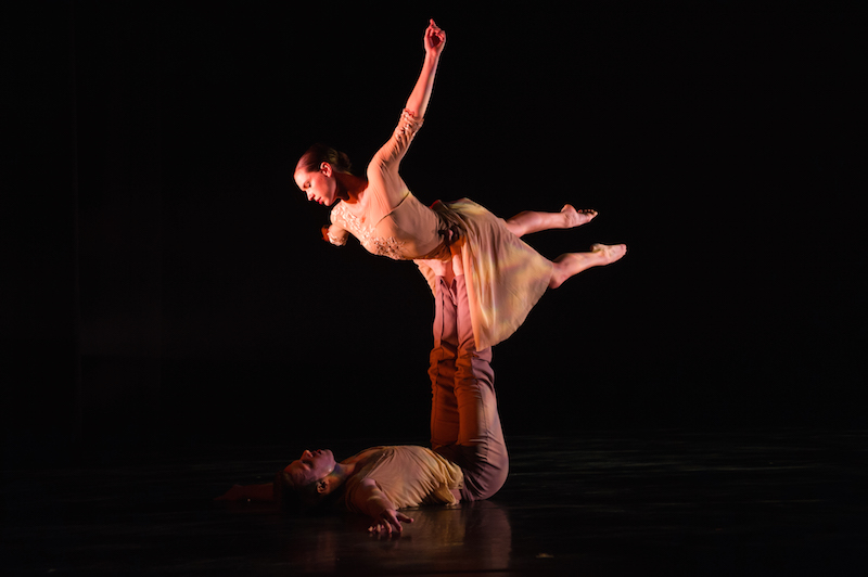 A man lays on his back with his feet extended and supports his partner above him. The female dancer, in a costumed leotard and skirts appears to be floating in air save for the fact her partner is supporting her by his feet.