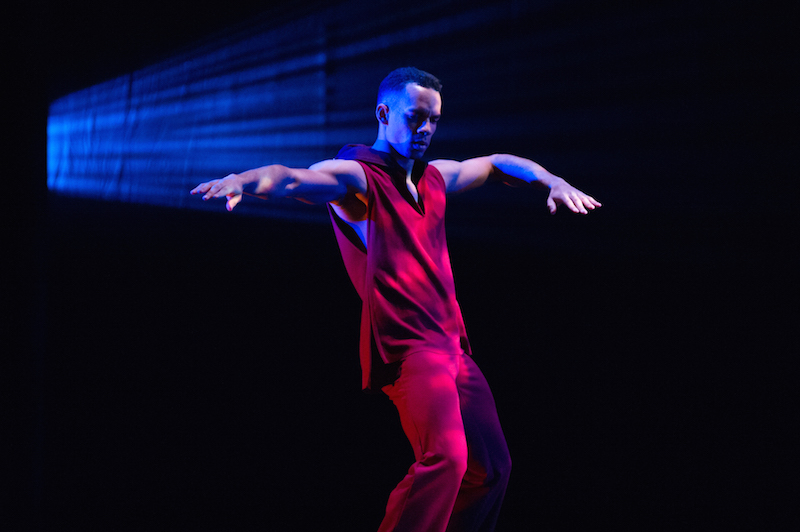 A dancer in a red tunic and pants bends his knees and extends one arm while his other is bent at an angle.