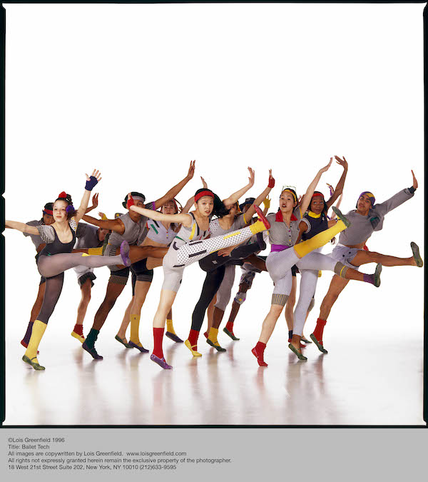 A group of Ballet Tech students in colorful leotards, tights, shoes and leggings, lift their right leg and flex their foot. They look out at the camera