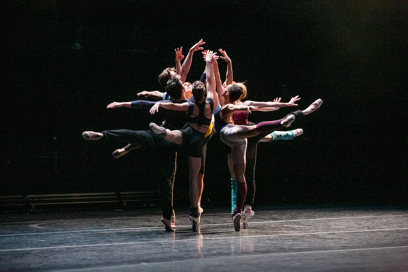 Dancers in colorful leotards and leg warmers pique in arabesque facing into a small circle