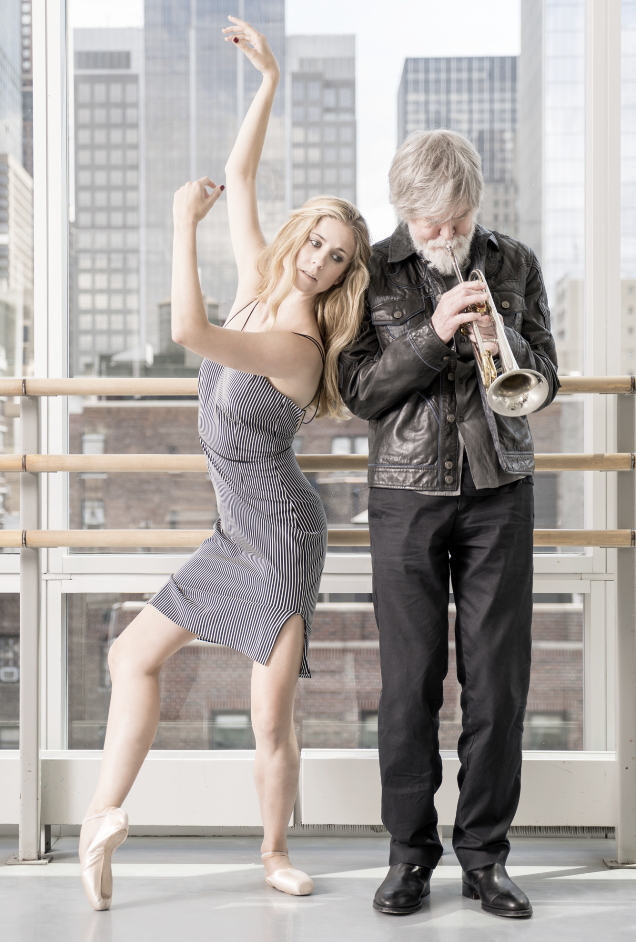 Michele Wilens in a black and white strapeless dress and pointe shoes leans against musician Tom Harrell who plays a trumpet