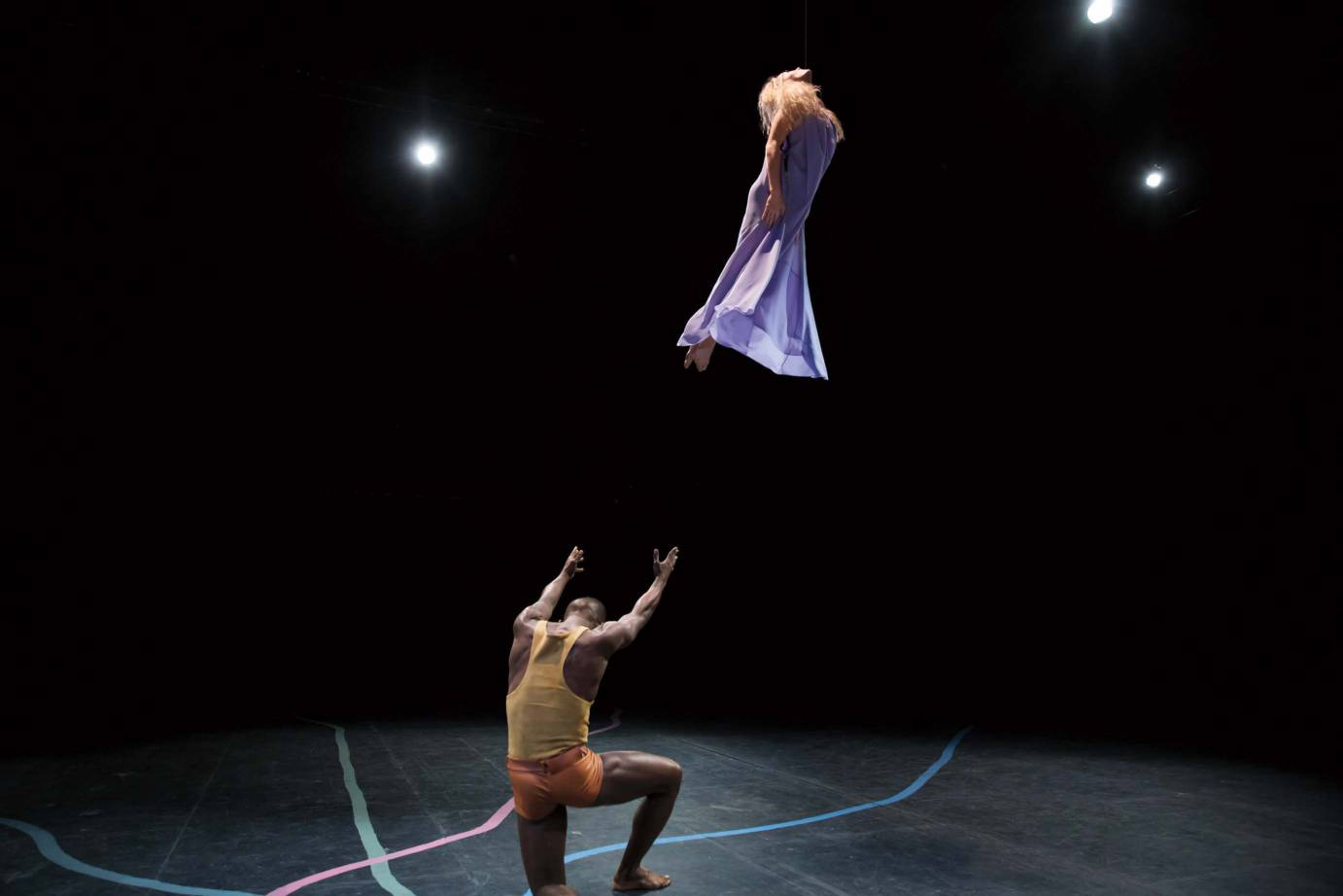 A male dancer propelling a female dancer clad in a purple dress into the air.