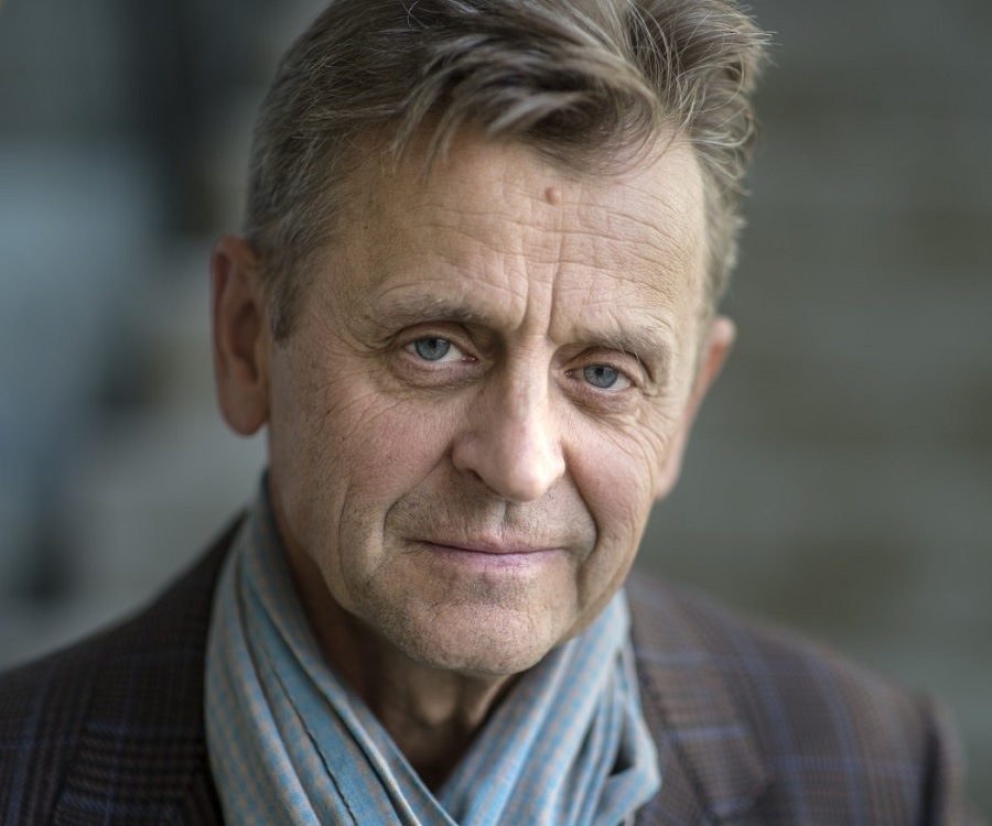 Portrait of Mikhail Baryshnikov wearing a light blue scarf and tartan jacket..