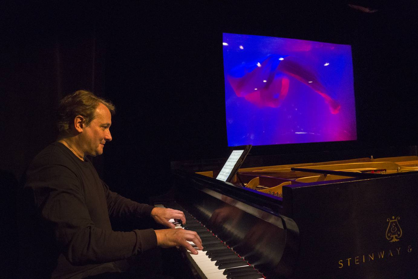 Christopher O'Reilly sits at a Steinway piano in front of a magenta-illuminated aquarium.