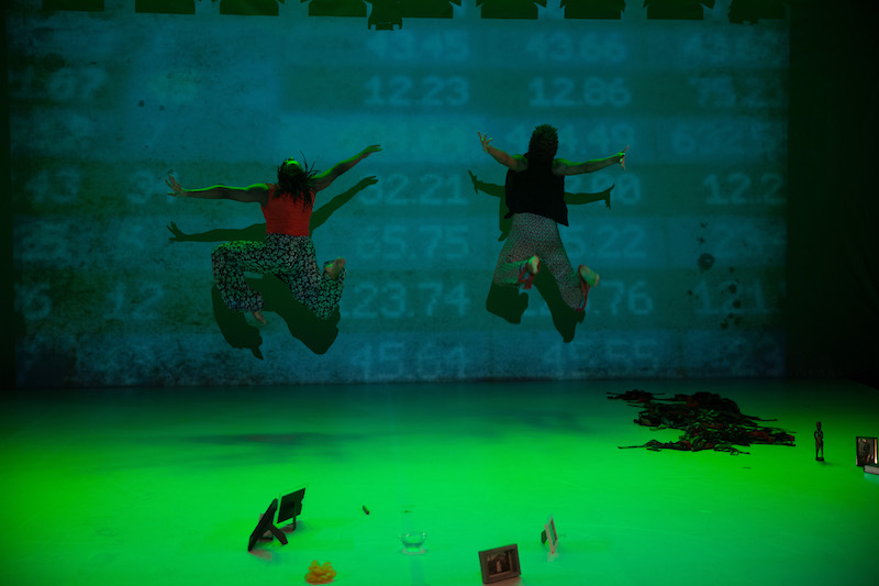 Two women, with their back facing the audience jump into the air. The stage is in lit in green hues. Numbers are subtlety projected onto the back wall.