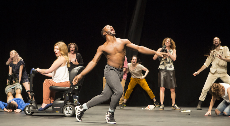 A cast of characters of different shapes and sizes smile and dance onstage. A shirtless man opens his mouth wide is at the center.