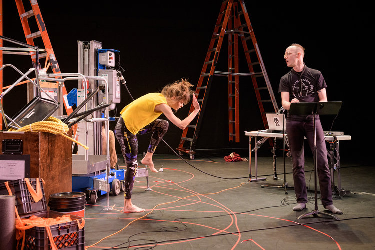 Joanna Kotze bends her body toward the ground while Ryan Seaton stands nearby in front of a music stand