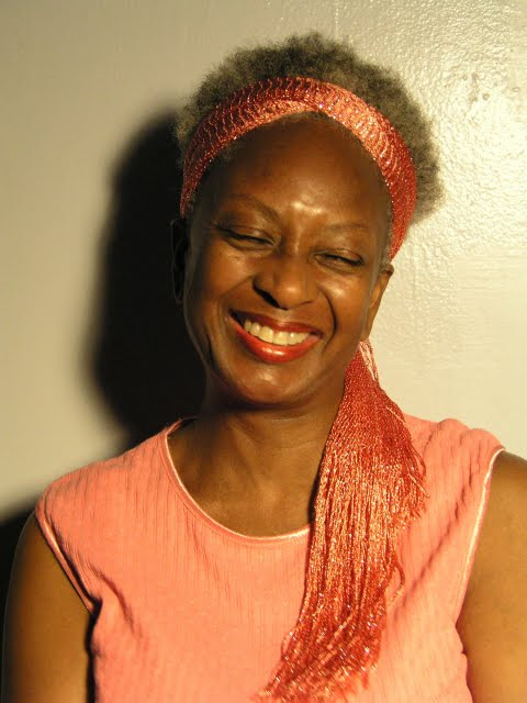 A portrait of Yaa Asantewaa wearing a peach colored blouse and scarf around her hair. She's smiling.