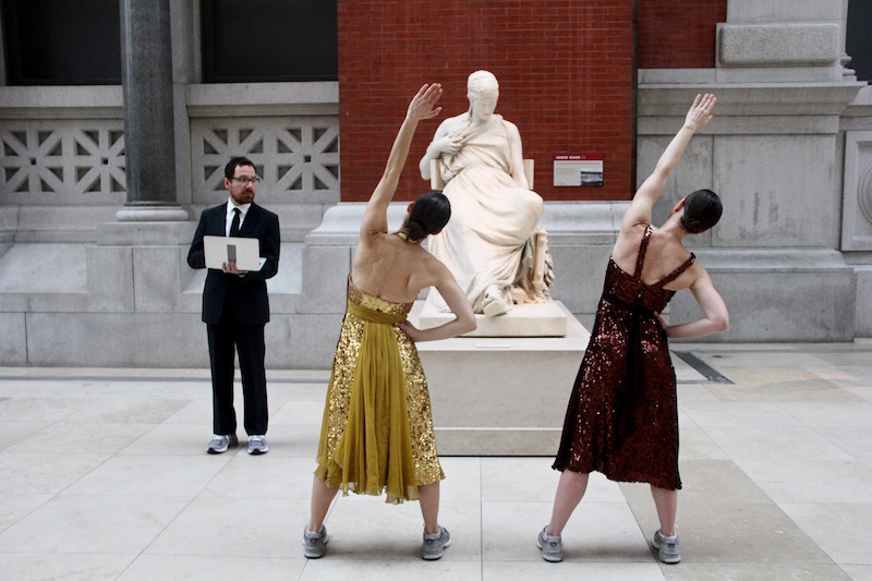 Two dancers stretch in front of a statue as a man in sneakers and a tux looks on with a laptop in his hand