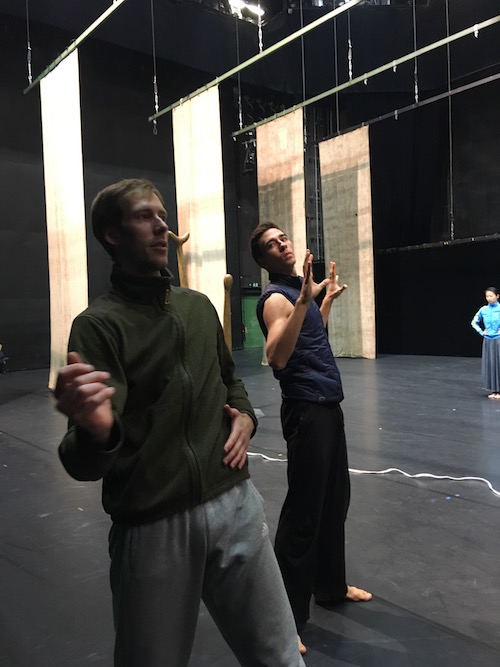 Two male dancers in sweats practice onstage.