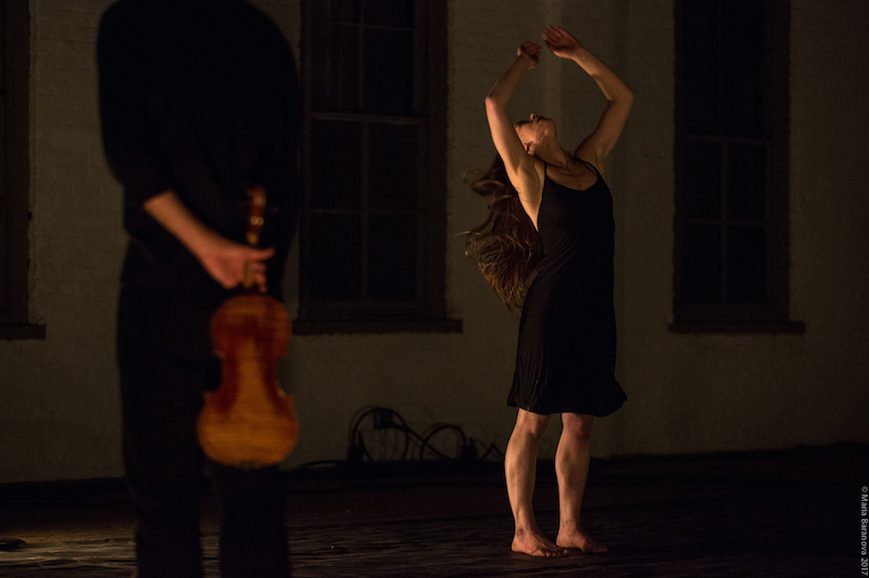 A woman in a black tank dress raises her arms above her head. A man dressed all in black holds a violin behind her back.