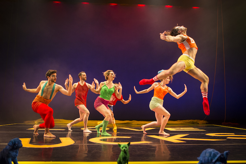 A dancer in the foreground leaps high into the air; his arms outstretched and head and chest lift to the ceiling. A group of dancers in the background assume a lunge position with one arm flexed at the elbow in front of their body and the other bent behind them.