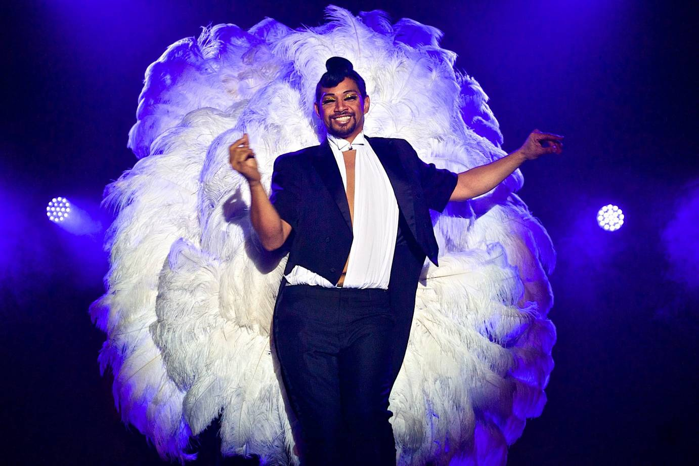 A bearded man in a suit and showgirl feathers