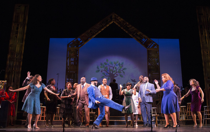 The 2016 cast of Cabin in the Sky. A man wearing a blue suit kicks his right leg out and his shoulders back