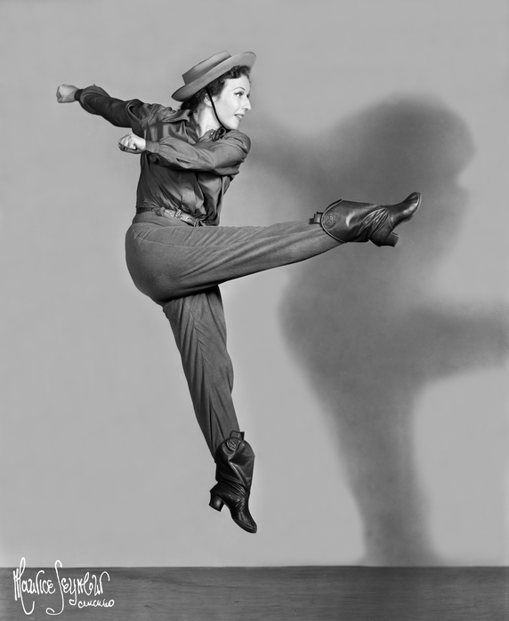 Agnes de Mille in Western inspired garb kicks high in the air. Her hands swing to the side of her.