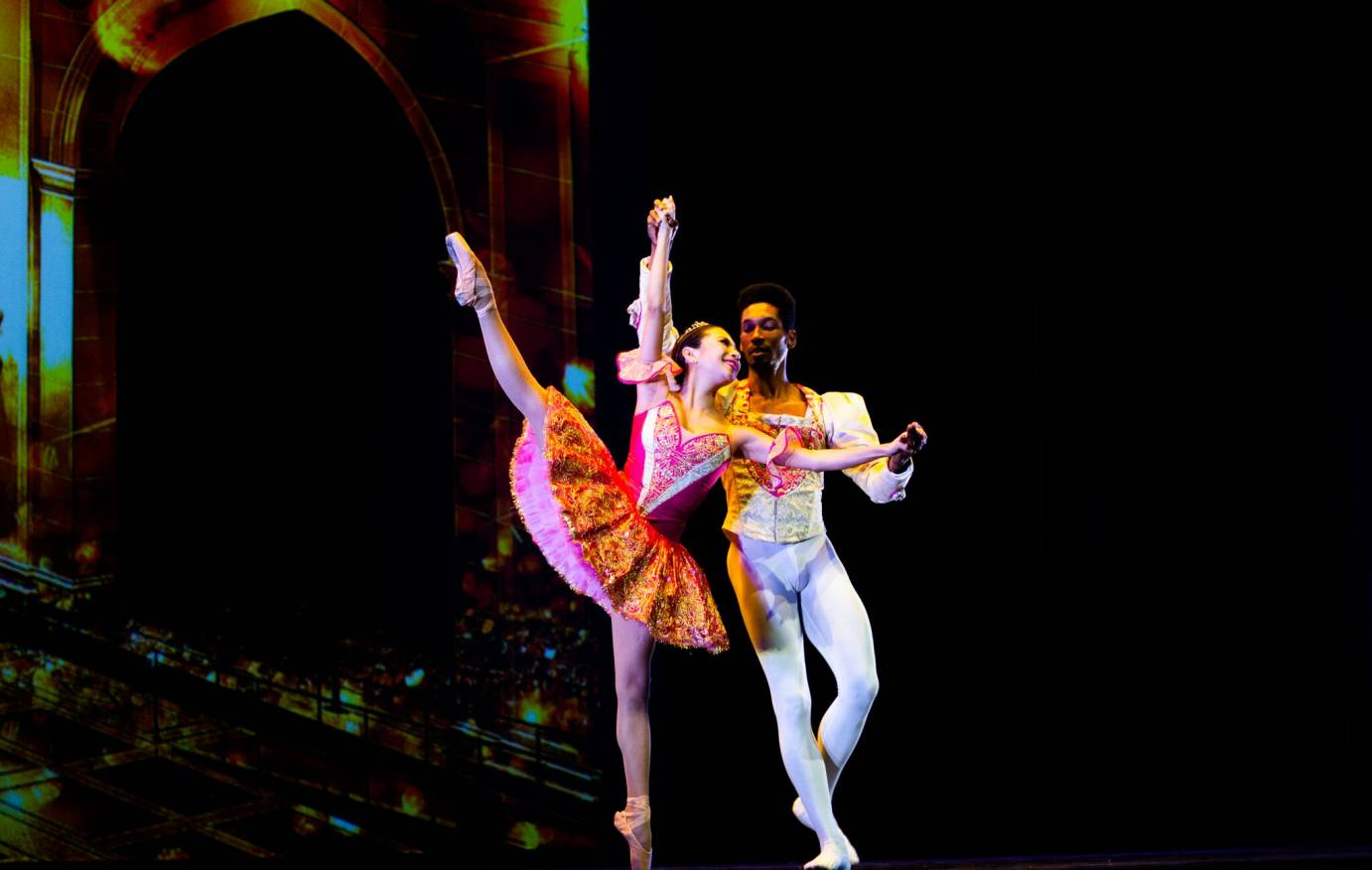 Expert ballet couple in candy colored costumes
